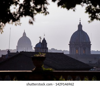A view across the city of Rome in the late evening. The two domes of St Peter's Basilica in the Vatican and Sant'Andrea della Valle can be seen silhouetted against the sky.