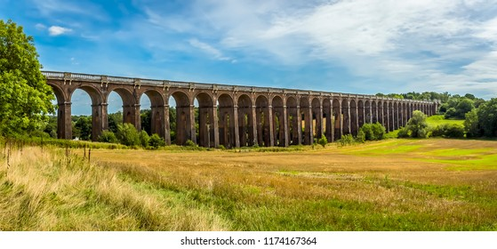 A view across a field towards the Ouse Valley viaduct in Sussex, UK on a summers day