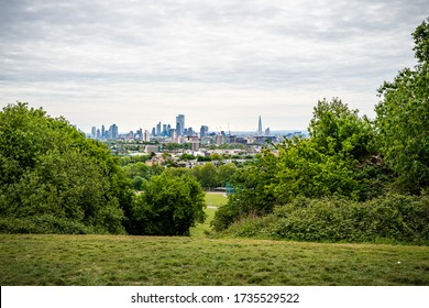 A view across the fields and trees to the City of London from the Parliament Hill Viewpoint in Hampstead Heath, London