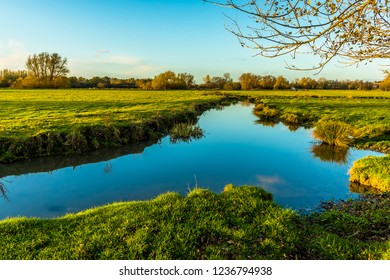 A view across the glassy surface of the River Stour on the western edge of Sudbury, Suffolk