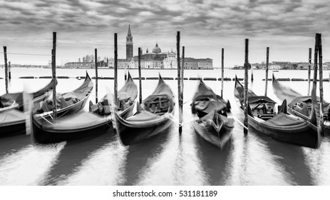 View across the Grand Canal in Venice with several gondolas in the foreground.  Black and white.