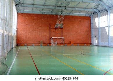 View across in indoor sports court with goalposts and a basketball hoop and net against a red brick wall, empty background view