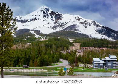 View from across Lake Levinsky to Big Sky mountain village, set amongst pine trees and dwarfed by the enormisity of Lone Mountain, Lone Mountain is in the Madison Range in the state of Montana, USA