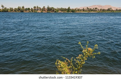 View across lareg wide river Nile at Luxor Egypt to West bank through rural countryside landscape