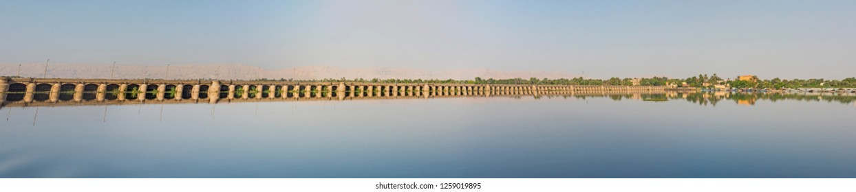 View across large wide river Nile in Egypt through rural countryside landscape with dam at Edfu