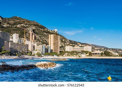 A view across Larvotto district in Monaco with sea and buildings including hotels lining the shore.