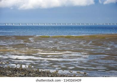 View across mudflats towards Oosterschelde estuary in the Netherlands and 5 kilometer long Zeeland Bridge