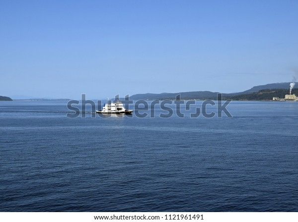 view across the ocean towards a ferry with the Powell River pulp mill and coastline in the background, British Columbia Canada