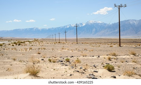 View across Owens Valley, with Highway 190 disappearing in the distance towards Olancha and the Sierra Nevada, also showing Olancha Peak and the southern tip of Owens Dry Lake.