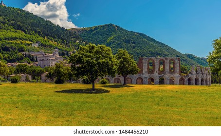 A view across a park towards the remains of the Roman amphitheater in front of the city of Gubbio, Italy in summer