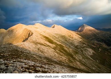 View across the peaks of the Pirin Mountains in Bulgaria with Vihren, Kutelo and Banski Suhodol joined by the Koncheto Saddle under a stormy cloudy sky with a shaft of sunlight illuminating the range