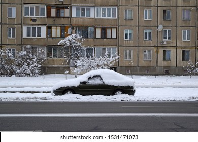 A view across the road of a car in a winter snow city