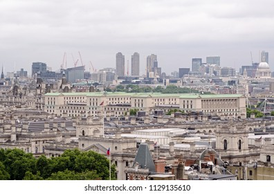 View across the roofs of Whitehall with the green copper rooftop of the Ministry of Defence dominating the scene.  Barbican tower blocks , St Paul's Cathedral and the City of London in the distance.