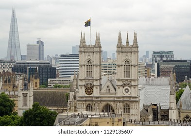 View across the rooftops towards the great West facade of the historic Westminster Abbey in London with the modern ladmaks of the Shard and Canary Wharf in the background.