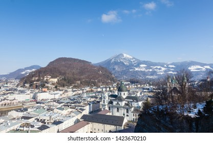 The view across Salzburg's Old Town in Austria.  Collegiate Church can be seen in the foreground and in the background are Kapuzinerberg a hill to the east of the city and Gaisberg a mountain.