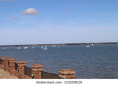 View across sea under a blue sky with brick wall in the foreground, showing yachts at The Stone, St Lawrence Bay, Essex