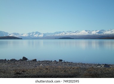 A view across a still blue lake to distant snow-capped mountains. The sky is blue. The shore of the lake is covered in pebbles. The mountains are reflected in the water.