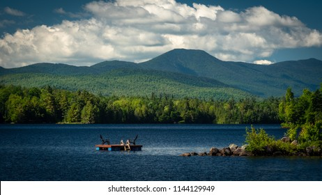 View across Union Falls Pond in the Adirondacks looking toward the McKenzie Mountain Wilderness in the distance on a summer morning