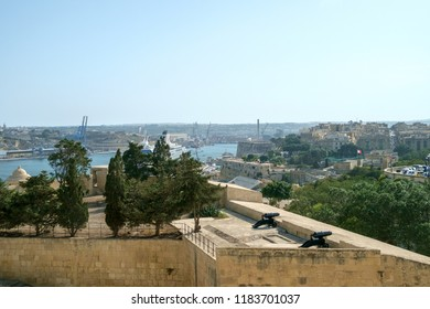 View across the Valetta cityscape past an old gun emplacement in Valletta, Malta.