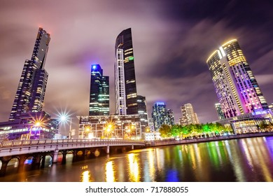 A view across the Yarra river at the landmark of Melbourne downtown at night with cloudy sky.