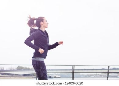 View at active young beautiful woman running in urban enviroment