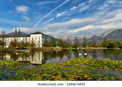 View of the Admont Abbey and the Lily-covered pond with a couple of swans on a sunny autumn day. Town of Admont, district of Liezen, Gesause National Park, state of Styria, Austria.