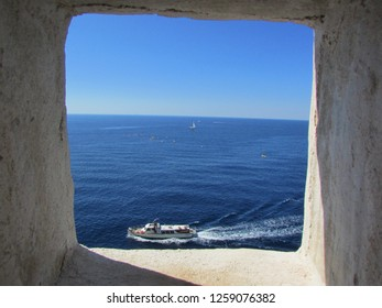 View to adriatic sea and boat from loophole in Dubrovnik city wall, Croatia