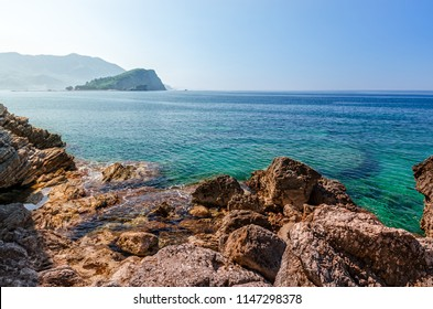 View of the Adriatic Sea and the island of St. Nicholas in the Budva Bay. The stony shore of a beautiful azure sea. Seascape.