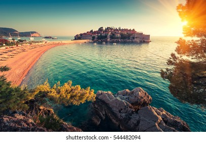 View in the Adriatic sea and Sveti Stefan at sunset. Milocer Park. Coast Budva Riviera. Montenegro.