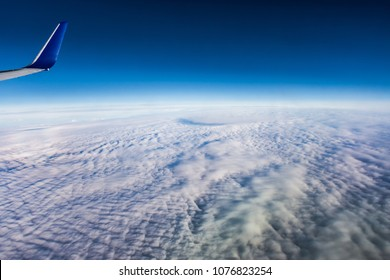 View from an aeroplane on a thick cover of clouds, with an airoplane wing in the corner