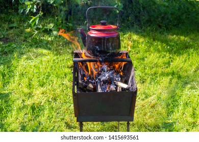 View from afar.Red kettle on an open fire on a green lawn.  The concept of survival in the absence of traditional sources of energy. Irony or joke.Heating the water in the old kettle