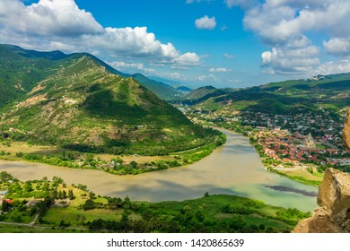View from afar of the town of Mtskheta, the UNESCO world heritage city and the Mtskheta river in Georgia under blue sky