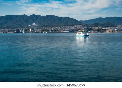View of an afternoon boat ride (ferry) on the ocean to the UNESCO World Heritage Site, the shrine island of Itsukushima - Miyajima in Japan near Hiroshima bay with the famous red asian torii gate.