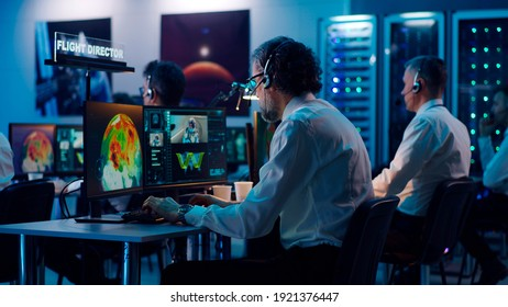 View of aged man giving advice to mature coworker using computer during spacecraft launch in flight control center