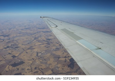 View of the  agricultural land from the air  flying to Perth, Western Australia   with the wing of the plane  in view  on a cloudy afternoon in summer Wet Season is beautifully exhilarating.