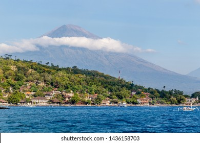 View of Agung volcano from the ocean. Villages, houses, traditional fishing boats jukung around. Amed, Karangasem Regency, Bali, Indonesia