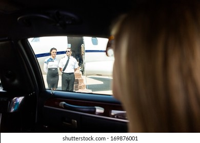 View of airhostess and pilot standing against private jet through limousine window
