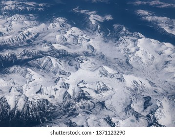 View from airplane on Earth surface - snow-capped mountains.