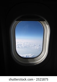 View from the airplane seat -- window with sky, clouds
