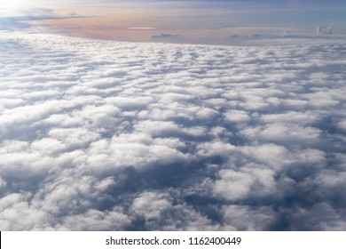 View from airplane window above the clouds with blue sky and cloudscape in sunlight morning. white wispy cirrus and cirrostratus clouds