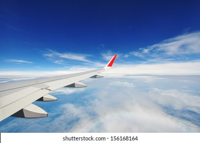 View from airplane window with blue sky and white clouds