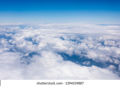 View from airplane window to the sky with beautiful snow-white and fluffy clouds through which the Earth is viewed