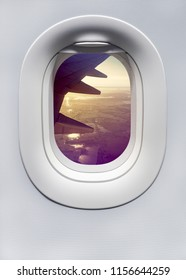 View from the airplane window with sunset sky and plane wing. White porthole of the aircraft with top view landscape and sunlight at sunrise for your concept of passenger air transport.
