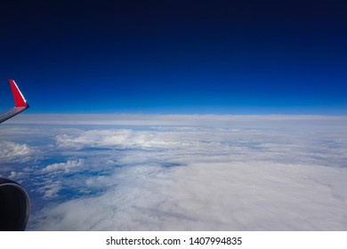 View from airplane window. Wing of an airplane flying above the clouds. Deep blue sky