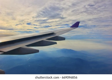 View from airplane window. Wing of an airplane flying above land and clouds