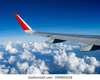View from airplane windows from passenger, beautiful cloud group and blue sky. Wing aircraft in altitude during flight.Concept of travel and business trip. Traveling concept.