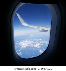 View of airplane wing and blue sky from airplane window. (1)