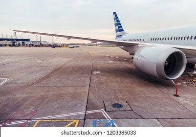 View of airplane wing and engine on tarmac at airport