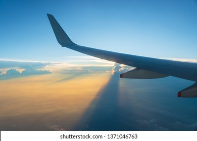View of airplane wing and sunset sky. Plane in flight, clouds project long shadows.