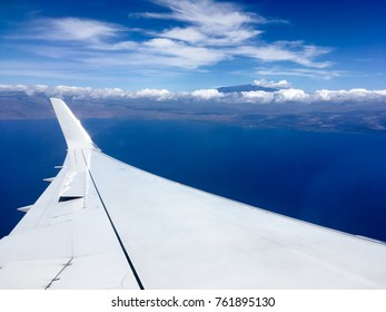 View of airplane wing with winglet, Pacific Ocean, and Mauna Kea mountain in the distance, before landing at Kona Big Island, Hawaii